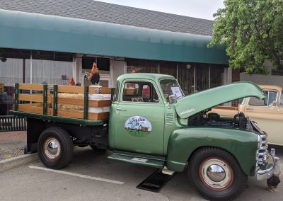 Green classic truck with the hood open parked on the street.