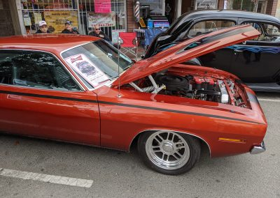An orange classic car with the hood open parked on the street.